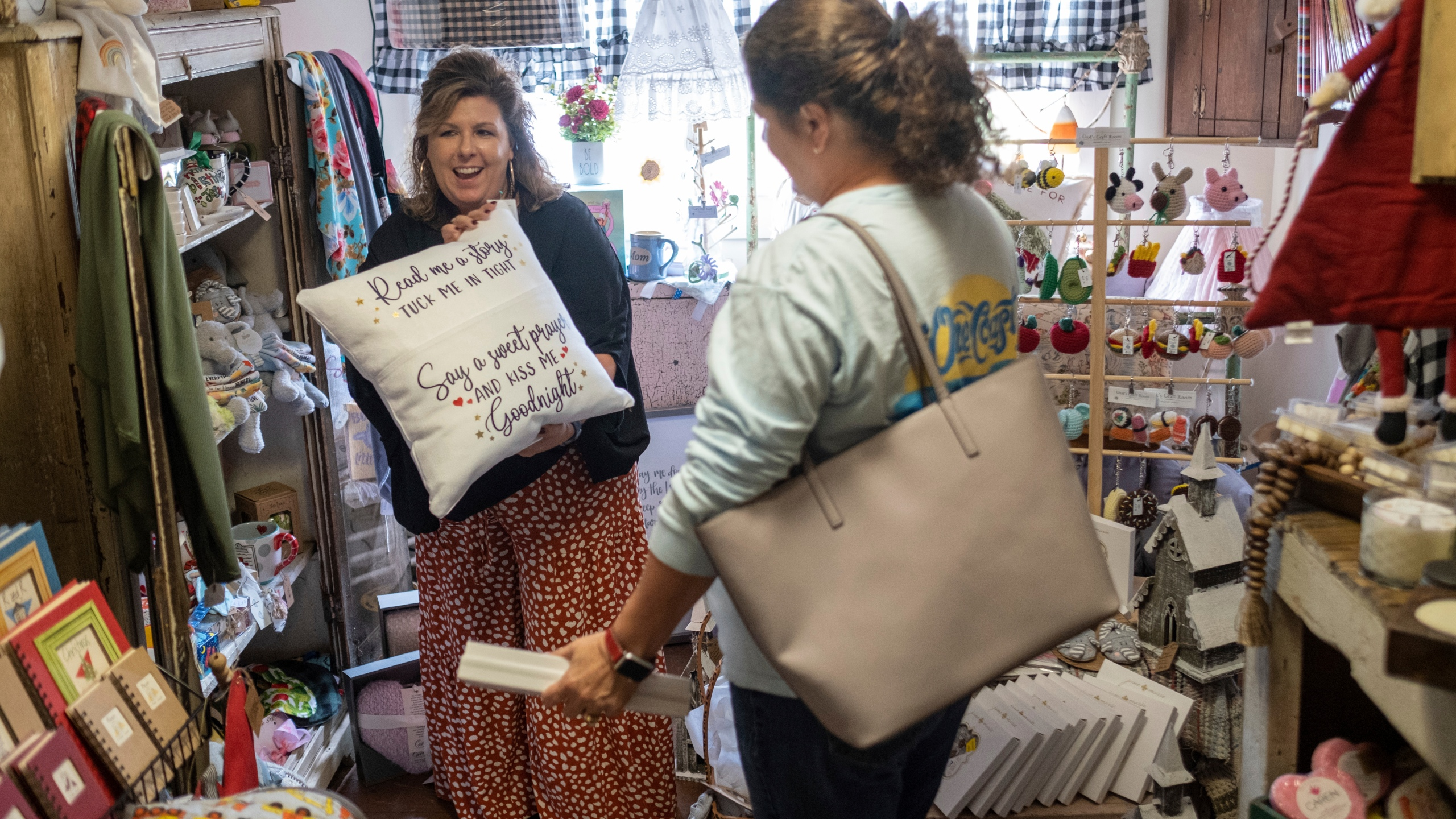 Ginger Pigg suggests a gift to a customer in her gift boutique The Perfect Pigg in Cumming, Ga. on Thursday afternoon, Oct. 22, 2021. She says she is struggling to get products to her store in a timely way. (AP Photo/Ben Gray)