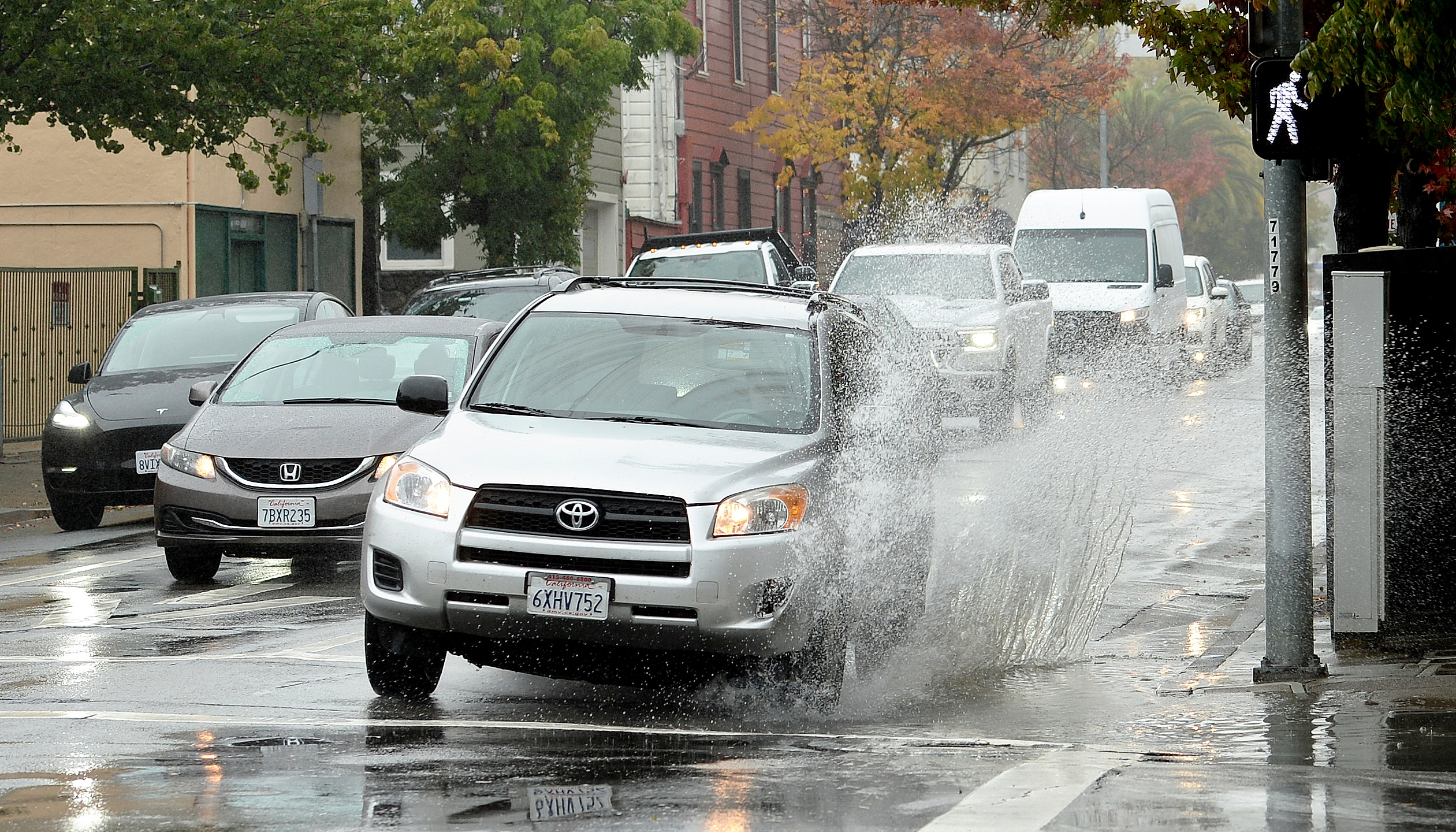 A car makes a big splash driving over a puddle on Third Street in San Rafael, Calif. on Thursday, Oct. 21, 2021. (Sherry LaVars/Marin Independent Journal via AP)