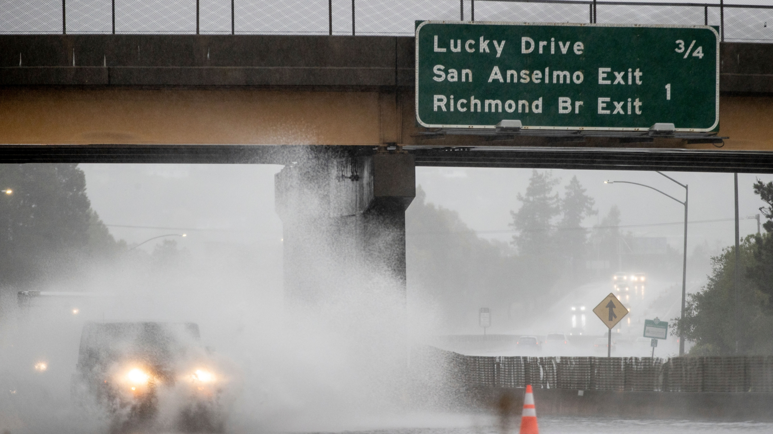A car drives on Highway 101, which is partially flooded in Corte Madera, Calif., Sunday, Oct. 24, 2021. (AP Photo/Ethan Swope)