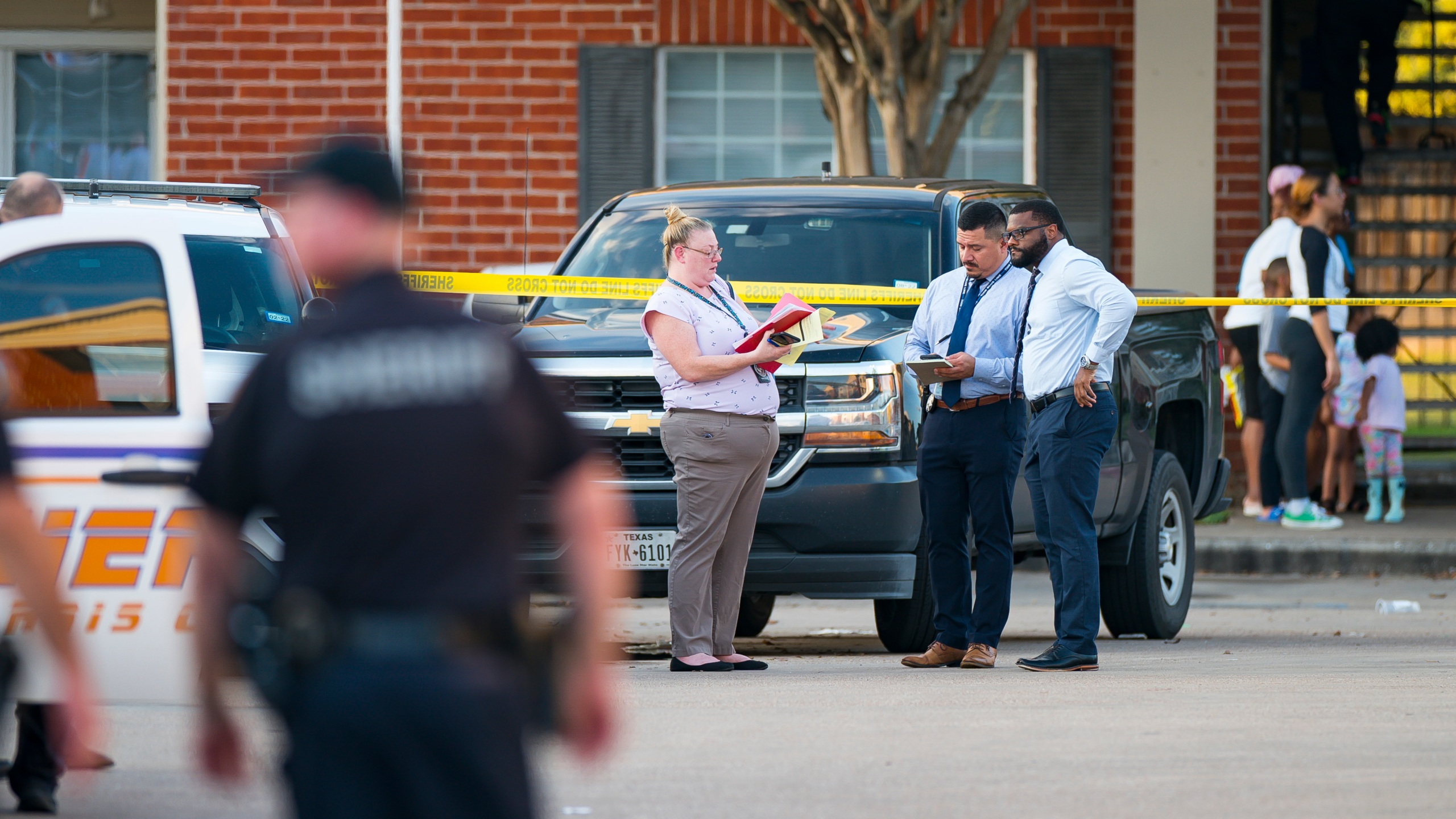 Law enforcement officials investigate a scene where, according to Harris County Sheriff Ed Gonzalez, three juveniles were found living alone along with the skeletal remains of another person, possibly a juvenile, in a third floor apartment at the CityParc II at West Oaks Apartments on Sunday, Oct. 24, 2021, at in west Houston. (Mark Mulligan/Houston Chronicle via AP)