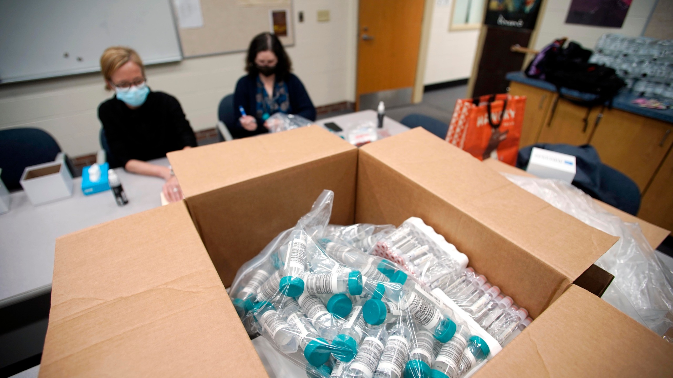 In this Oct. 25, 2021, file photo, registered Nurse Carisa Vincent, and Hope Rose Kelly prepare pool tests for COVID-19 behind a mountain of supplies at Reid Middle School in Pittsfield, Mass. (The Berkshire Eagle via Associated Press)