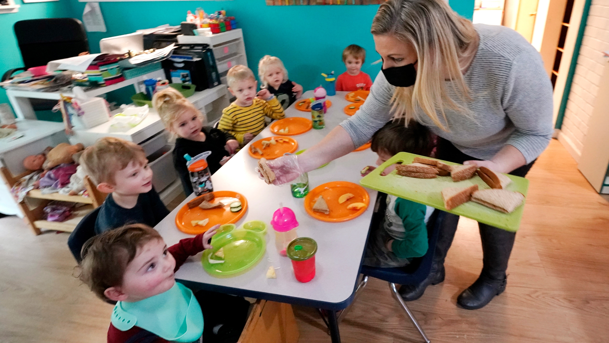 Amy McCoy serves lunch to preschoolers at her Forever Young Daycare facility, Monday, Oct. 25, 2021, in Mountlake Terrace, Wash. Child care centers once operated under the promise that it would always be there when parents have to work. Now, each teacher resignation, coronavirus exposure, and day care center closure reveals an industry on the brink, with wide-reaching implications for an entire economy's workforce. (AP Photo/Elaine Thompson)