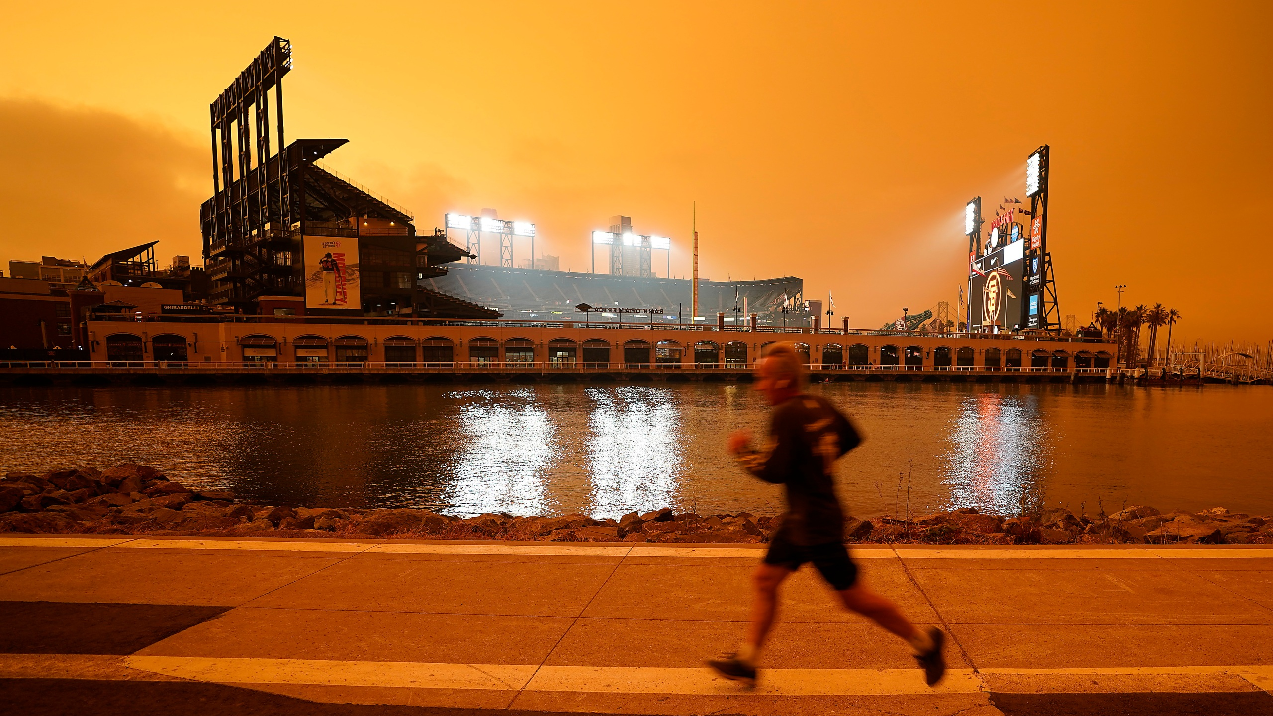 In this Wednesday, Sept. 9, 2020 file photo, a jogger runs along McCovey Cove outside Oracle Park in San Francisco, under darkened skies from wildfire smoke. Health problems tied to climate change are all getting worse, according to two reports published in the medical journal Lancet on Wednesday, Oct. 20, 2021. An unprecedented Pacific Northwest and Canadian heat wave hit this summer, which a previous study showed couldn't have happened without human-caused climate change. (AP Photo/Tony Avelar)