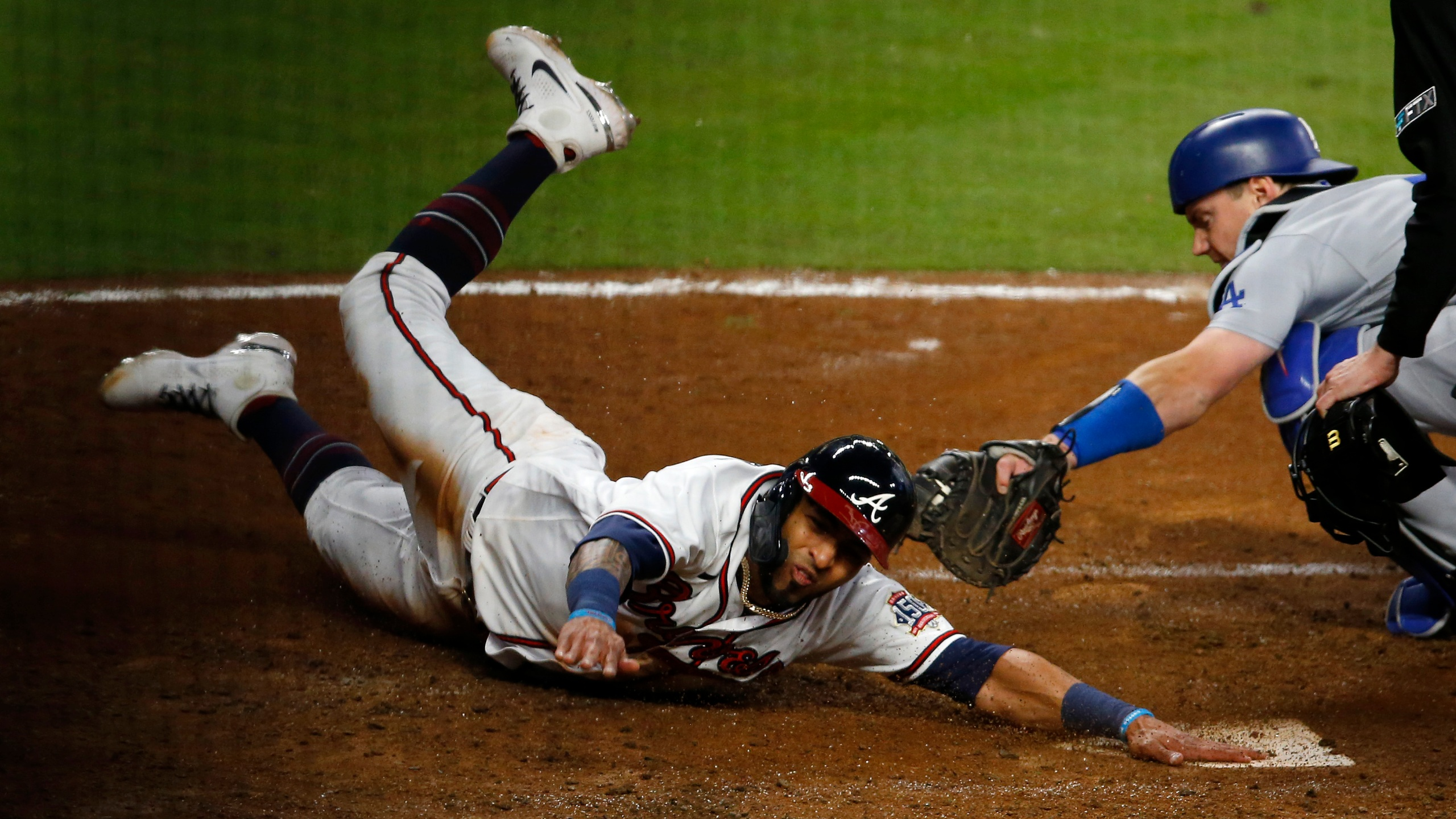 Eddie Rosario #8 of the Atlanta Braves slides safely past Will Smith #16 of the Los Angeles Dodgers to score in the eighth inning of Game Two of the National League Championship Series at Truist Park on October 17, 2021 in Atlanta, Georgia. (Photo by Michael Zarrilli/Getty Images)