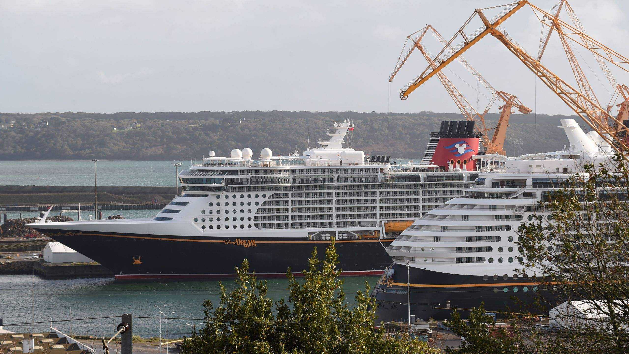 A picture taken on October 26, 2020 shows the Disney Dream liner (L), the third liner of the Disney Cruise Line, and the Disney Fantasy (R), owned by the Walt Disney Company cruise operator in Brest harbour, western France. (JEAN-FRANCOIS MONIER/AFP via Getty Images)