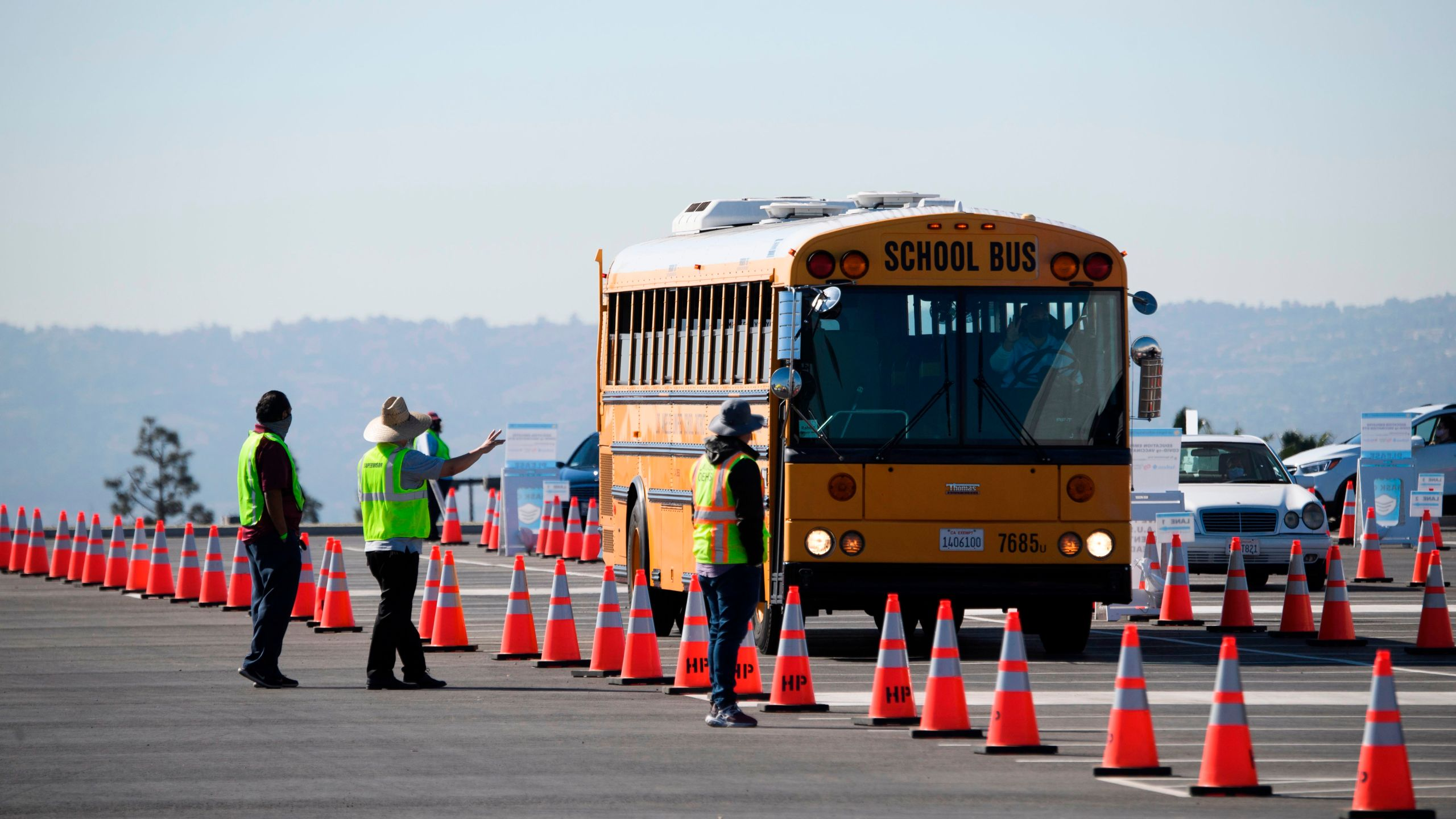 A school bus transporting education workers arrives at a mass vaccination site near SoFi stadium on March 1, 2021 in Inglewood. (PATRICK T. FALLON/AFP via Getty Images)