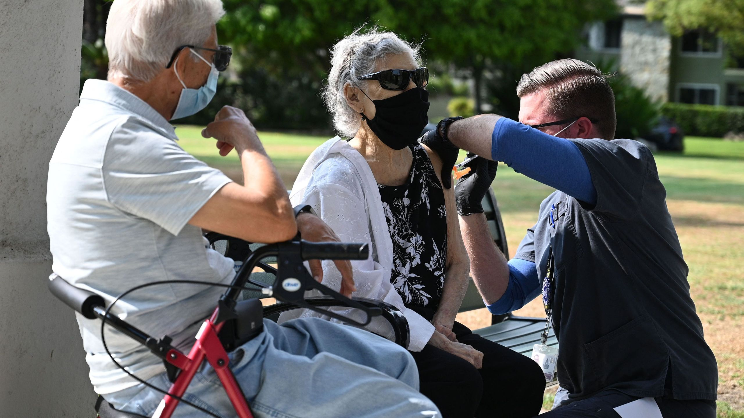 Nurse administers a third booster dose of Pfizer COVID-19 vaccine to Armida Gomez, 81, as her husband Jose Gomez, 80, waits for his turn during a vaccination clinic hosted by Tournament of Roses and the Pasadena Department of Public Health on Aug. 19, 2021 . (ROBYN BECK/AFP via Getty Images)