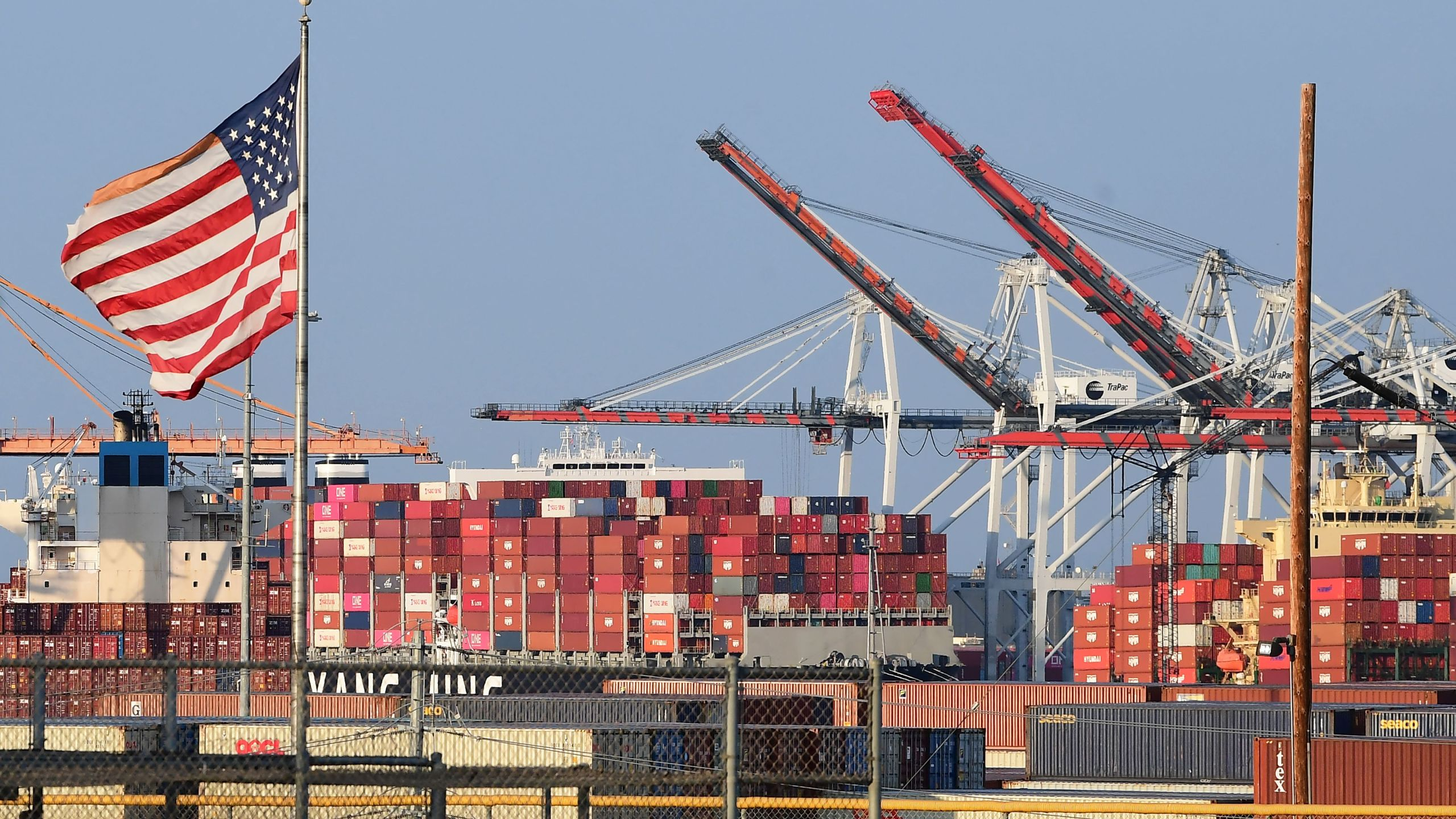 A US flag flies near containers stacked high on a cargo ship at the Port of Los Angeles on September 28, 2021 in Los Angeles, California. - A record number of cargo ships are stuck floating and waiting off the southern California coast amid a supply chain crisis which could mean fewer gifts and toys for Christmas this year as a combination of growing volumes of cargo, Covid-19 related saftey measures and a labor shortage slow the handling and processing of cargo from each ship. (Photo by Frederic J. BROWN / AFP) (Photo by FREDERIC J. BROWN/AFP via Getty Images)