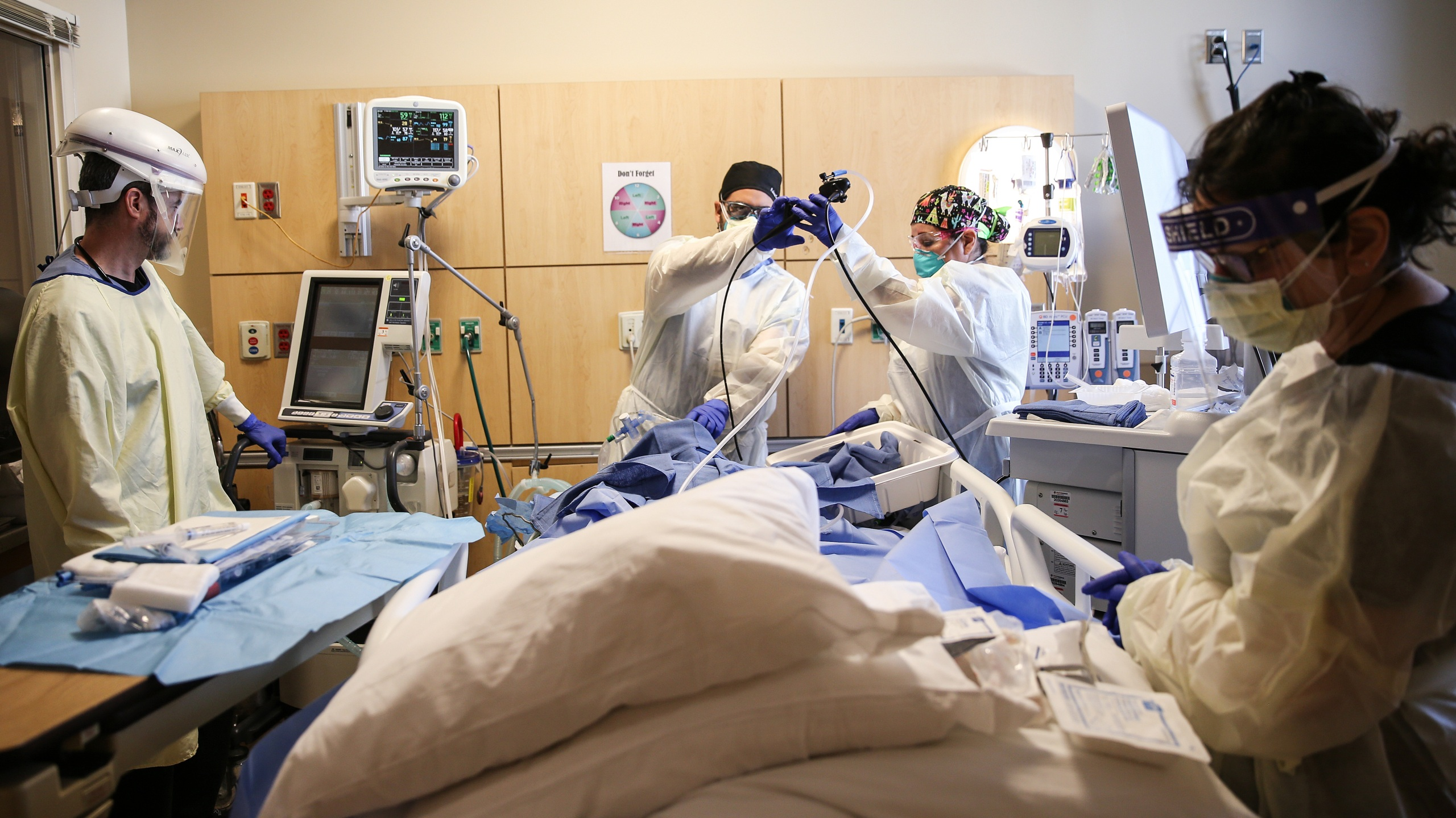 Clinicians perform a tracheostomy on a patient in a COVID-19 ICU in Mission Hills on Feb. 17, 2021 in Los Angeles. (Mario Tama/Getty Images)