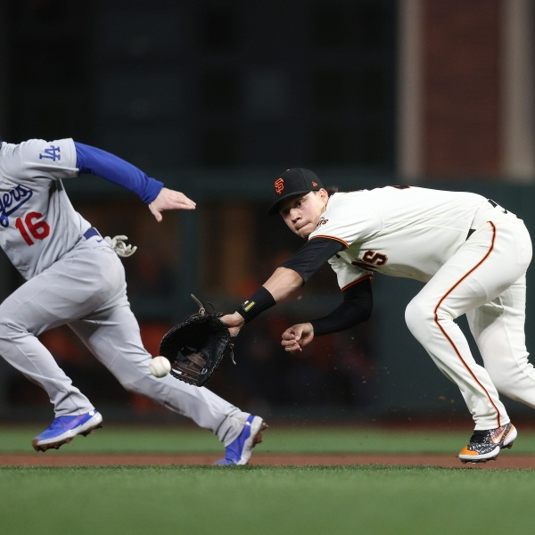Wilmer Flores of the San Francisco Giants makes a diving catch and throws out Will Smith of the Los Angeles Dodgers on a fielder's choice during the fifth inning of Game 1 of the National League Division Series at Oracle Park in San Francisco on Oct. 8, 2021. (Ezra Shaw / Getty Images)