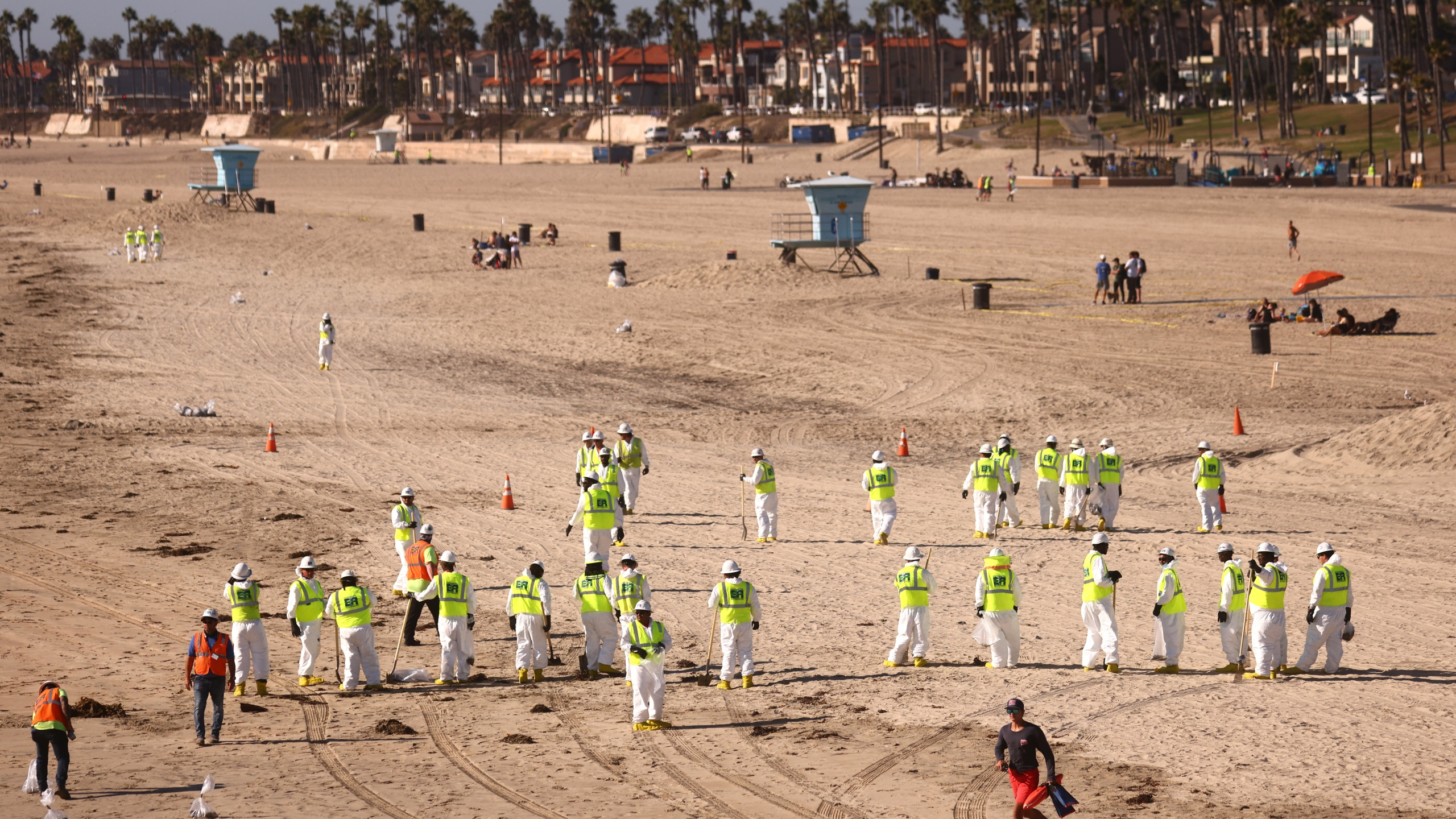 Cleanup workers search for contaminated sand and seaweed on a mostly empty Huntington Beach about one week after an oil spill from an offshore oil platform on Oct. 9, 2021. (Mario Tama/Getty Images)