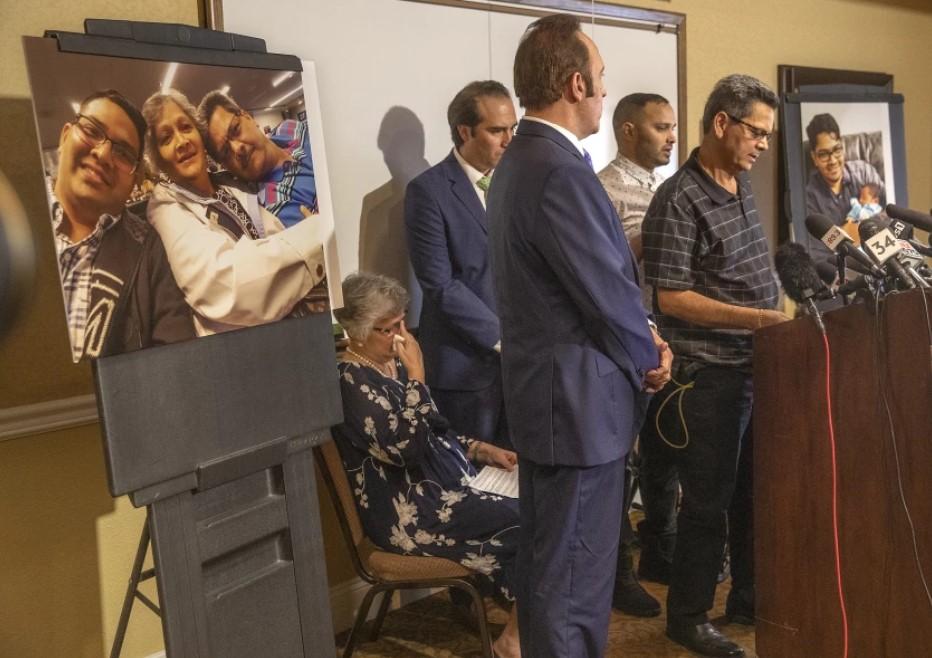 Russell French, right, announces in August 2019 that he and his wife, Paola, who is seated, were suing the city of Los Angeles and former LAPD Officer Salvador Sanchez over Sanchez's fatal shooting of their son, Kenneth French, inside a Costco in Corona. The photo at left shows Kenneth French in 2014 with his parents, who were also shot by Sanchez.(Mel Melcon/Los Angeles Times)