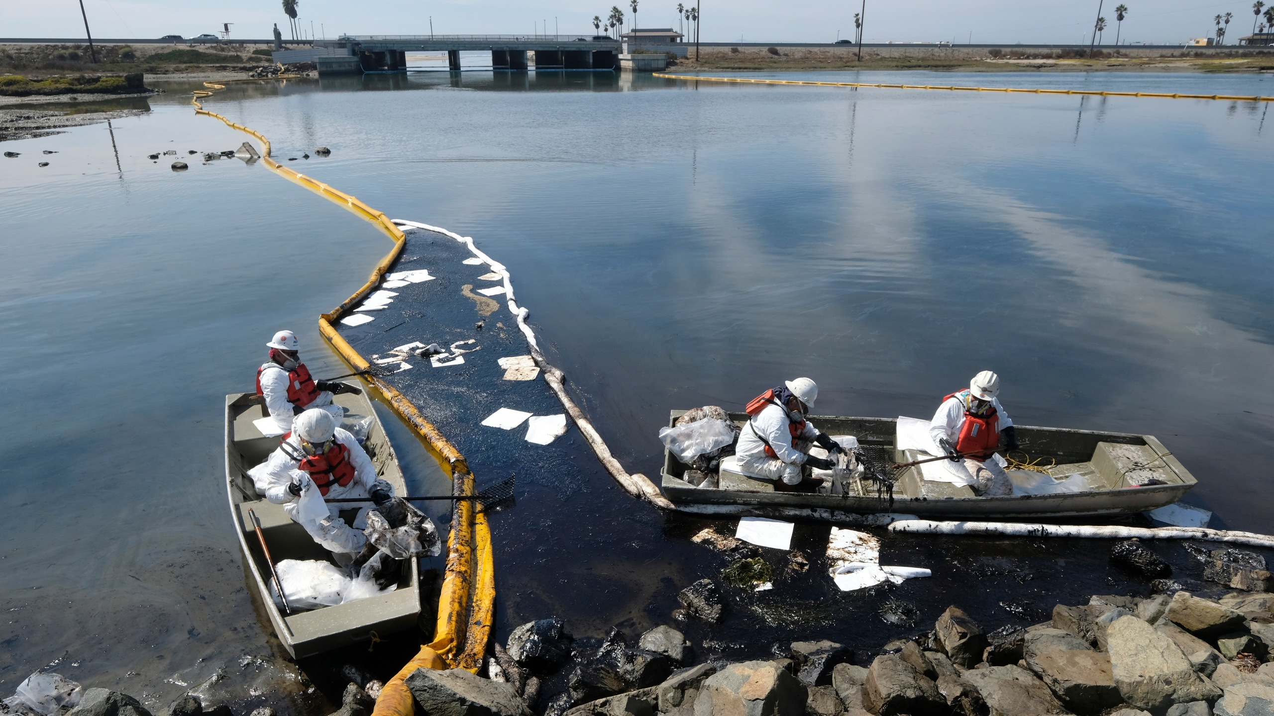 Cleanup contractors deploy skimmers and floating barriers known as booms to try to stop further oil crude incursion into the Wetlands Talbert Marsh in Huntington Beach, Calif., Sunday., Oct. 3, 2021. One of the largest oil spills in recent Southern California history fouled popular beaches and killed wildlife while crews scrambled Sunday to contain the crude before it spread further into protected wetlands. (AP Photo/Ringo H.W. Chiu)