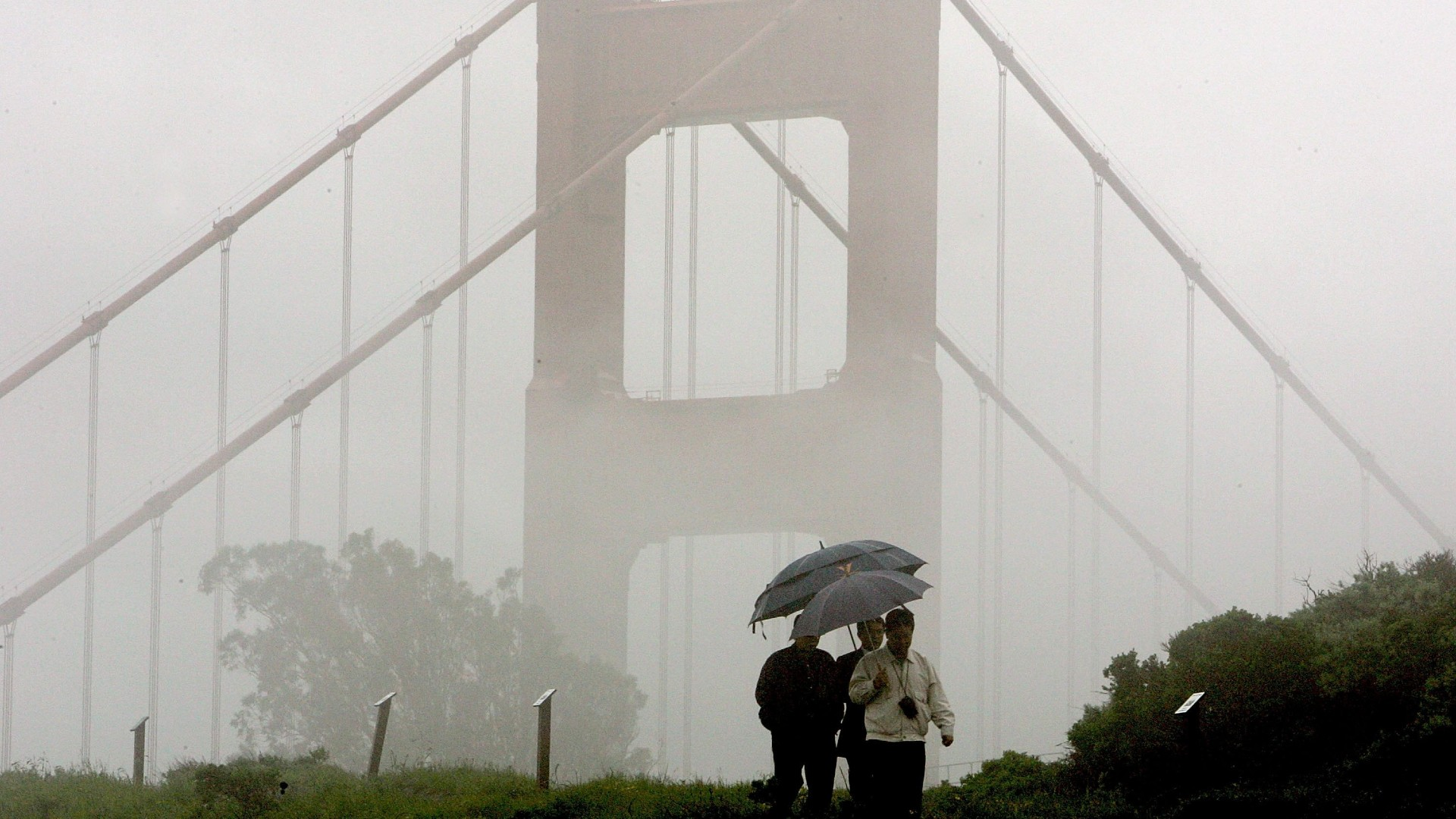 A group of men walk through the rain near the north tower of the Golden Gate Bridge April 12, 2006 in Sausalito. (Justin Sullivan/Getty Images)