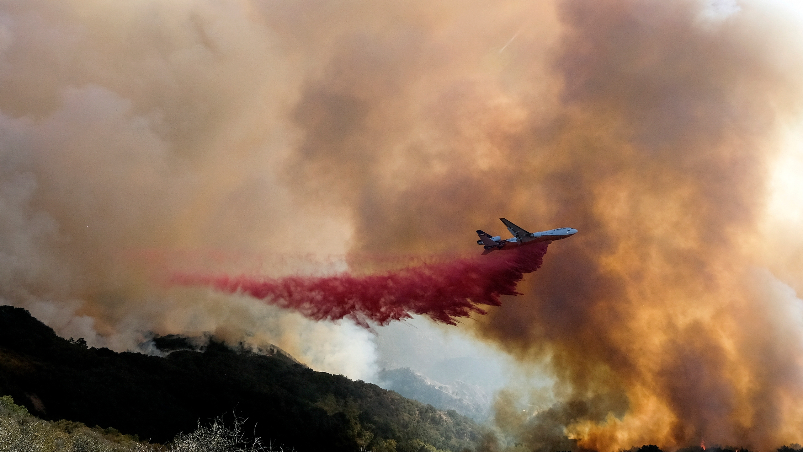 In this Oct. 13, 2021 photo, an air tanker drops retardant on a wildfire in Goleta, Calif. Firefighters persisted in making progress Saturday, Oct. 17, against a wildfire burning for a sixth day in Southern California coastal mountains. The Alisal Fire in the Santa Ynez Mountains west of Santa Barbara grew only slightly since Friday to nearly 27 square miles (69 square kilometers). It was 50% contained. (AP Photo/Ringo H.W. Chiu)