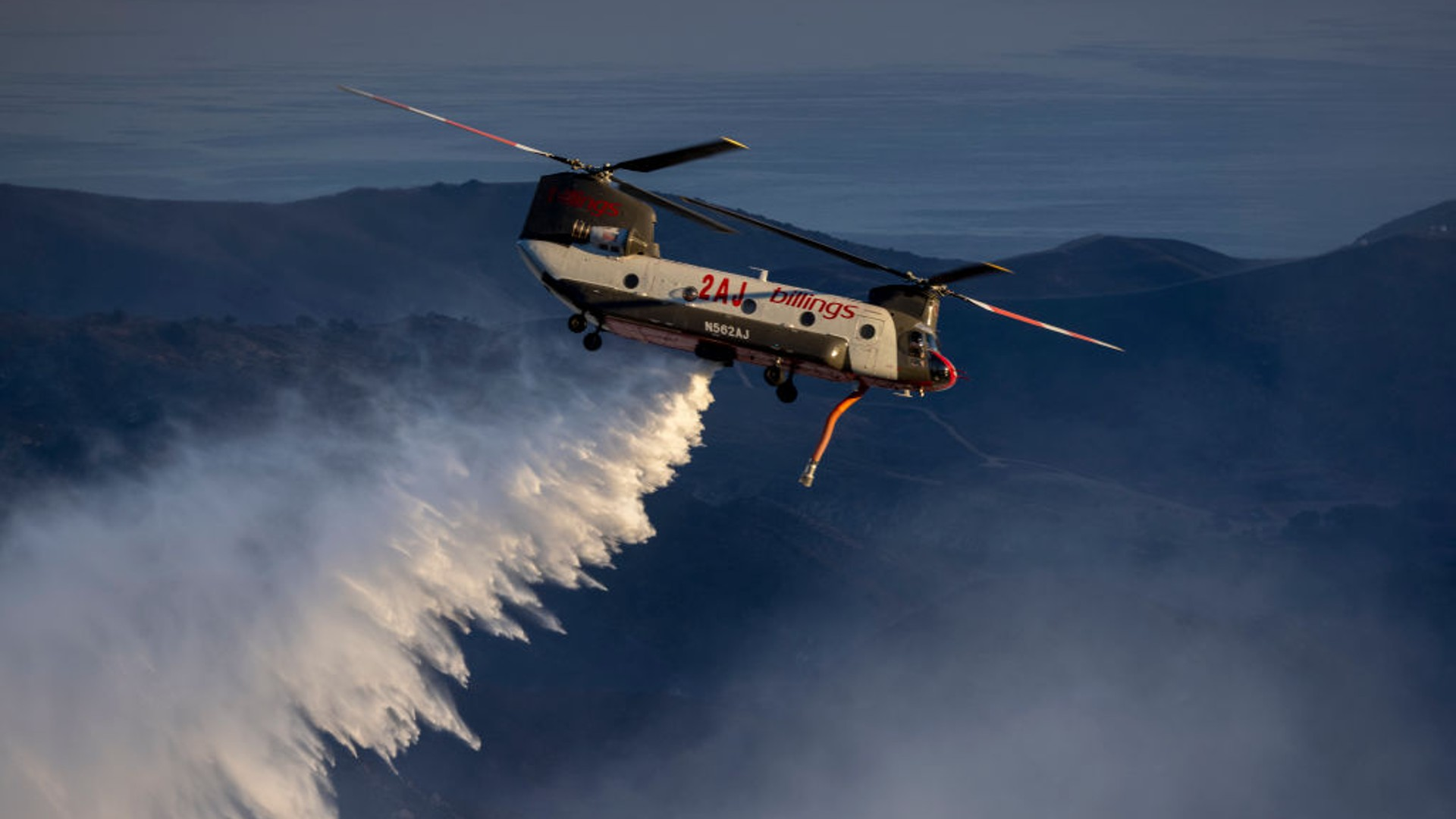 A firefighting helicopter makes a water drop as the Alisal Fire burns on October 13, 2021 near Goleta, California. (David McNew/Getty Images)
