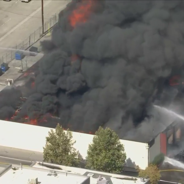 Crews work to put out a structure fire in Canoga Park on Oct. 18, 2021. (KTLA)