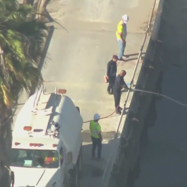 Public works officials work to deploy a deodorizer to assuage a foul smell coming from the Dominguez Channel in Carson on Oct. 15, 2021. (KTLA)