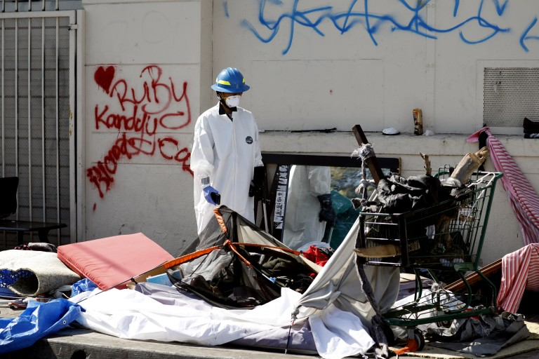 An L.A. sanitation worker cleans up around a homeless encampment on a sidewalk in South Los Angeles in 2018. (Francine Orr / Los Angeles Times)