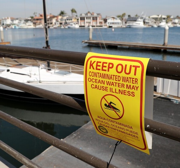 A sign warns pedestrians not to swim in the contaminated water at Huntington Harbour on Oct. 20, 2021, in Huntington Beach. (Kevin Chang / L.A. Times Community News)