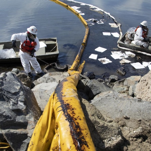 Workers with Patriot Environmental Services place containment booms to trap oil that flowed from an offshore pipeline leak into the Talbert Marsh in Huntington Beach on Sunday.(Myung J. Chun/Los Angeles Times)