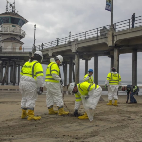Workers remove sand fouled by oil Thursday in Huntington Beach.(Irfan Khan / Los Angeles Times)