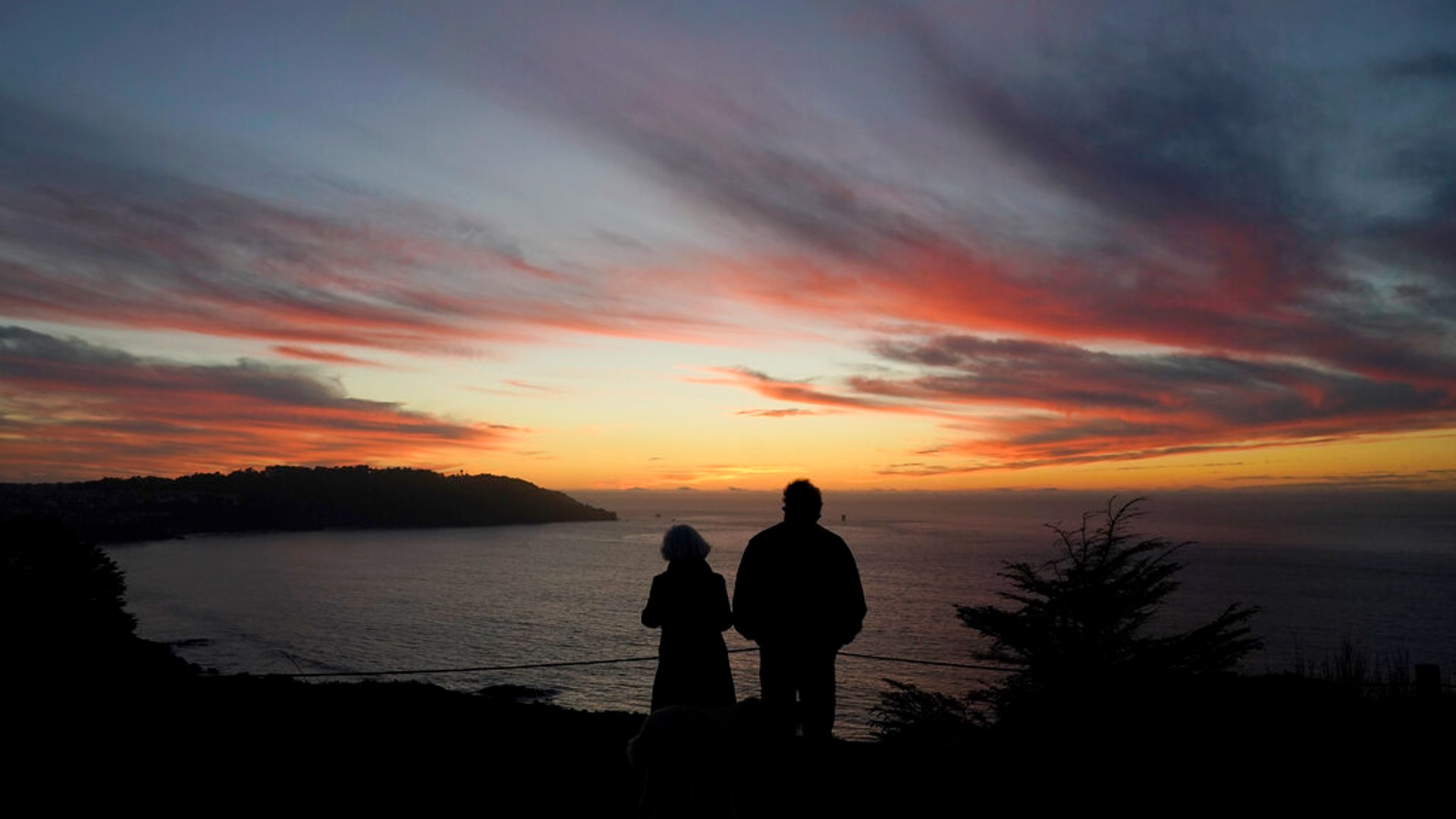 In this Dec. 21, 2020, file photo people watch as the sun sets from the Presidio in San Francisco. (AP Photo/Jeff Chiu, File)