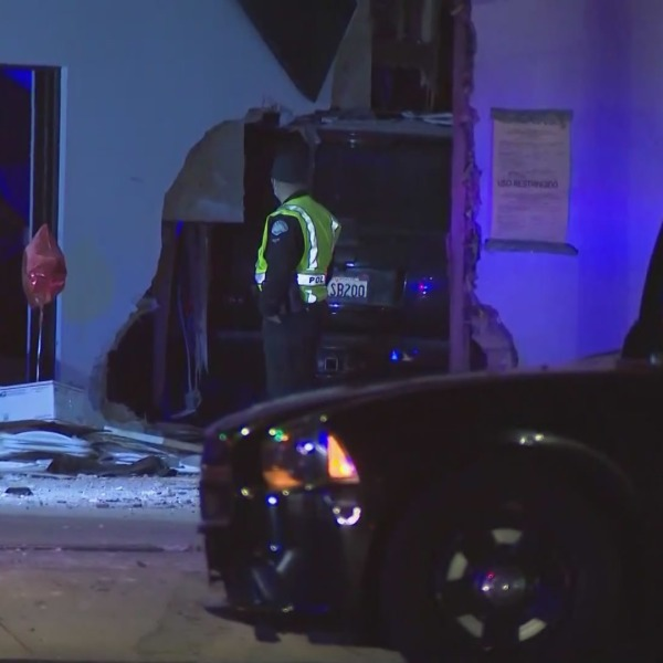 Police respond after a vehicle crashed into a building in Van Nuys. (KTLA)