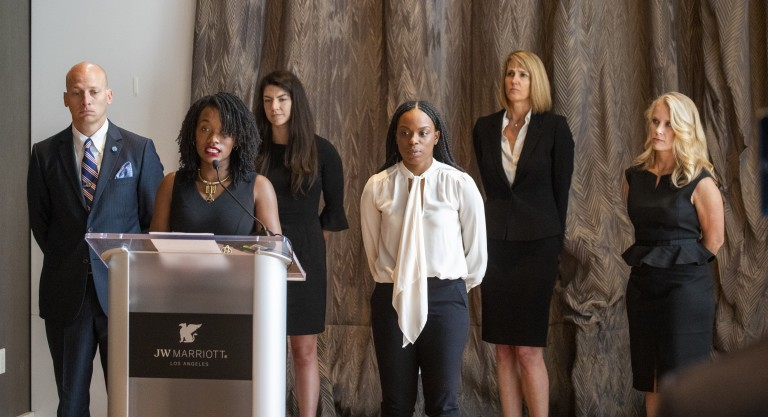 """Ja'Mesha Morgan, fourth from left, listens as Shernae Hughes, second from left, speaks while they and their attorneys hold a June 2020 news conference in L.A. to call on USC Board of Trustees Chairman Rick Caruso to """"keep his promise to release an internal investigation of the Tyndall scandal."""" (Allen J. Schaben/Los Angeles Times)"""