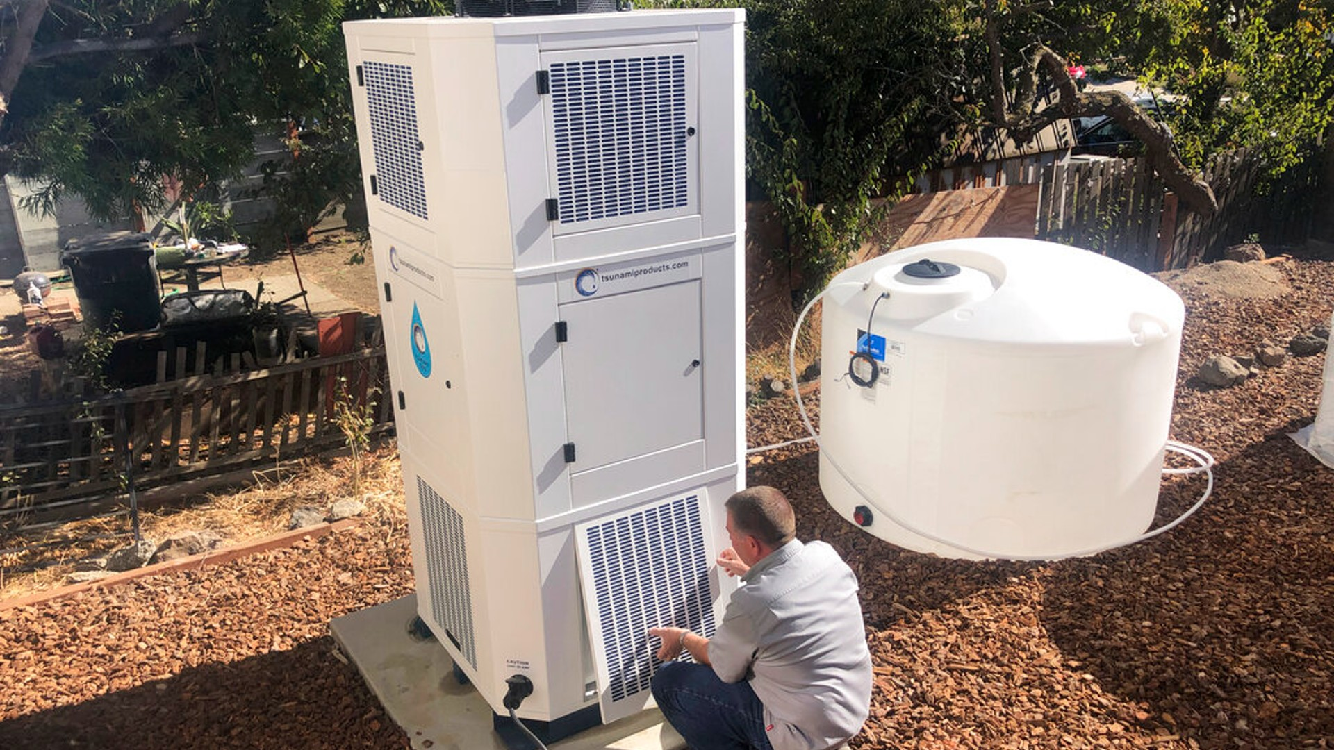 Ted Bowman, design engineer with Tsunami Products, installs a unit in homeowner Don Johnson's backyard in Benicia, Calif., Sept. 28, 2021. (AP Photo/Haven Daily)